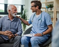 Male nurse sitting with a senior male patient having a good talk